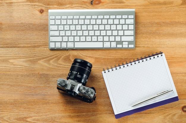 Teclado de computador, caneta e bloco de notas para notas, câmera em uma mesa de madeira. itens do fotógrafo no local de trabalho.