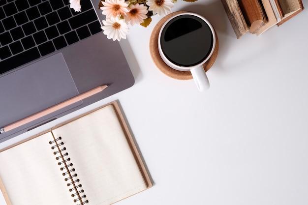 Teclado de computador da mesa de escritório da vista superior, livros, lápis e copo de café no espaço de trabalho.