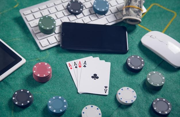 Teclado de computador, dinheiro, mouse, cartas de baralho e fichas