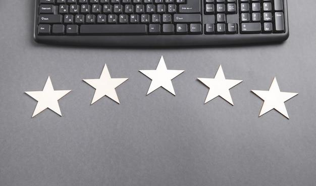 Teclado de computador e 5 estrelas de madeira. avaliação de serviço