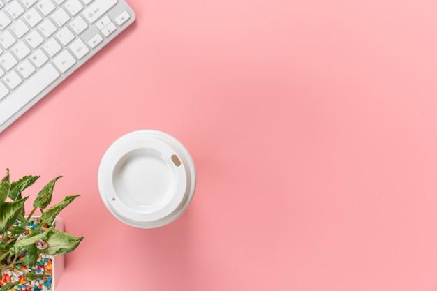 Teclado de computador e caneca de café sobre fundo rosa pastel