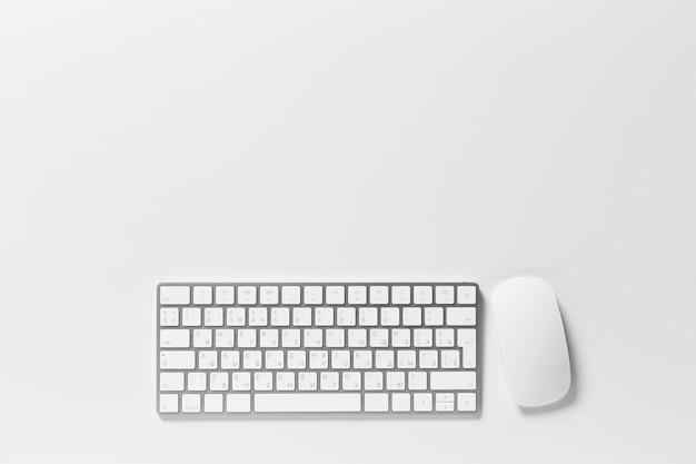 Teclado de computador e mouse em cima do desktop branco