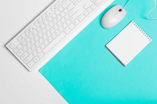 Teclado de computador e mouse sobre fundo de bloco de cores, interior do escritório