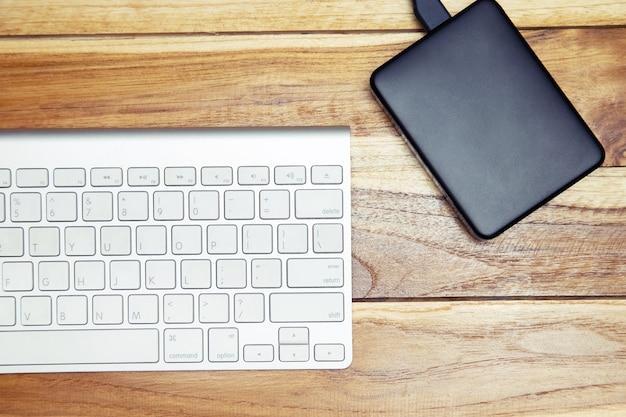 Teclado de computador moderno de alumínio de um laptop e disco rígido na madeira do escritório da mesa. dispositivos eletrônicos de tecnologia. vista do topo. hdd