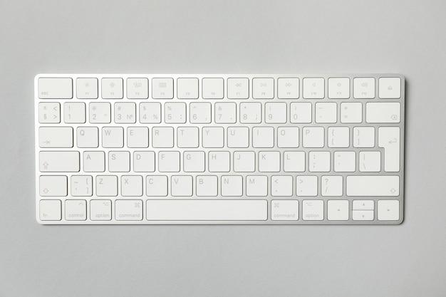 Teclado de computador moderno em fundo cinza, vista superior