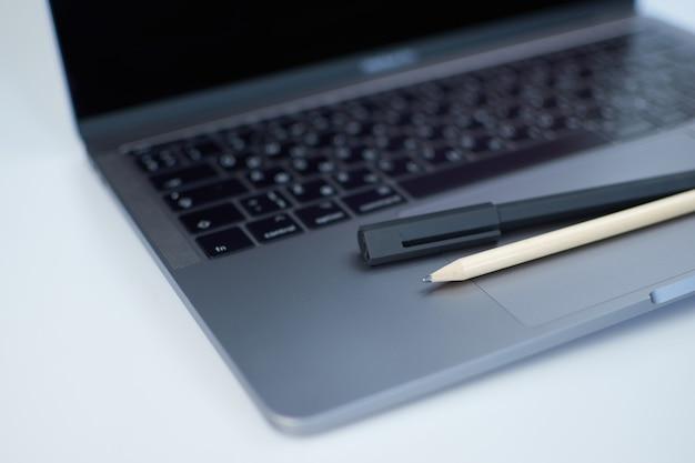 Teclado de computador portátil de close-up, caneta e lápis.