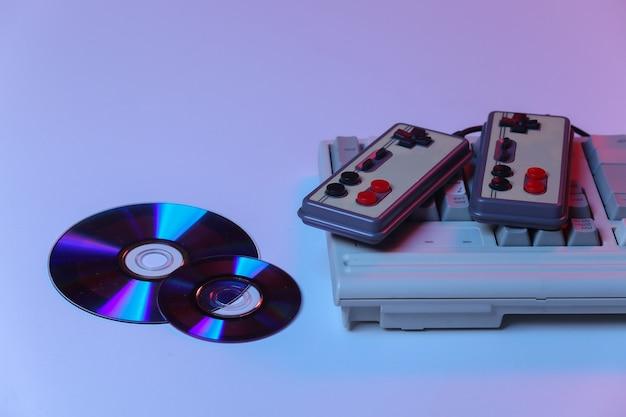 Teclado de pc antigo com gamepads, cd em néon gradiente rosa azul, luz holográfica. atributos retro anos 80