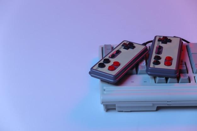 Teclado de pc antigo com gamepads em néon gradiente rosa azul, luz holográfica. onda retro