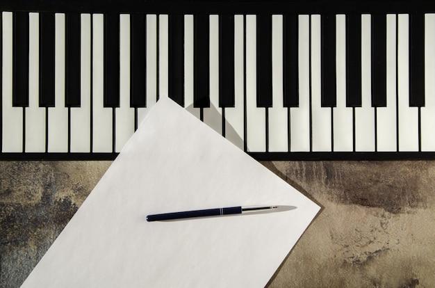 Teclado de piano, caneta e papel em branco. o conceito de compor música, canções, criatividade, aprendizagem.