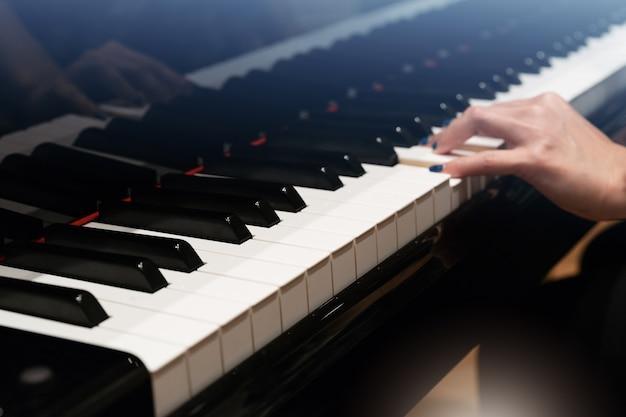 Teclado de piano clássico com borrão de mão de mulheres