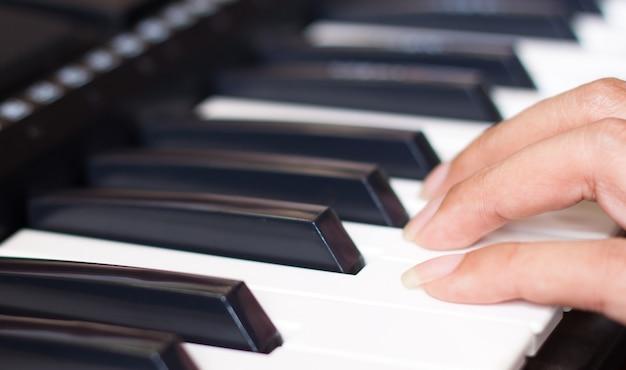 Teclado de piano com dedos de mulher
