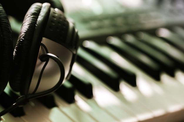 Teclado de piano com fones de ouvido, close-up