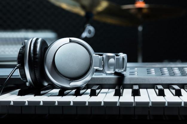 Teclado de piano com fones de ouvido para música, fones de ouvido no teclado de piano, close-up, fones de ouvido no fundo do piano elétrico pelo fundo de instrumentos de música.