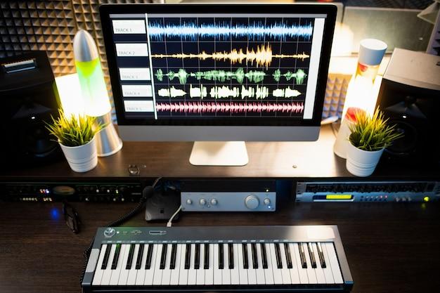 Teclado de piano e tela de computador com visualização de som de forma de onda no local de trabalho de músico moderno ou dj em estúdio