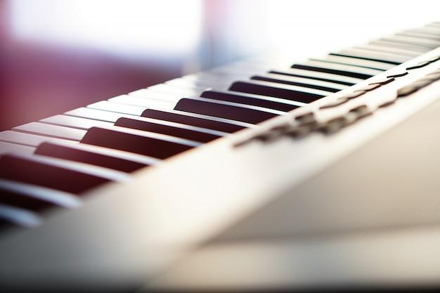 Teclado de piano sintetizador eletrônico na macro de raios do sol. raios de luz coloridos de alta tecnologia.