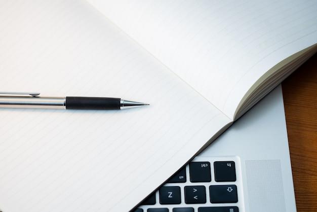 Teclado de um laptop de cima com um bloco de notas e uma caneta.
