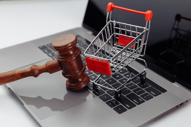 Teclado do laptop, carrinho de compras e martelo de leilão na mesa, conceito de leilão online.