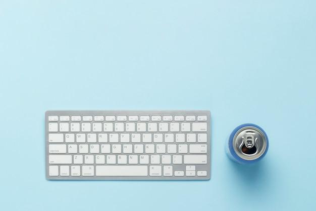 Teclado e lata com uma bebida, bebida energética sobre um fundo azul. conceito de negócio, trabalhando em um computador, jogando ps, filmes e programas de tv online. vista plana leiga, superior.