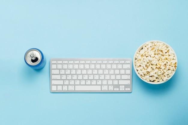 Teclado e lata com uma bebida, bebida energética, uma tigela de pipoca em um fundo azul. o conceito de assistir filmes, programas de tv, eventos esportivos online. vista plana, vista superior