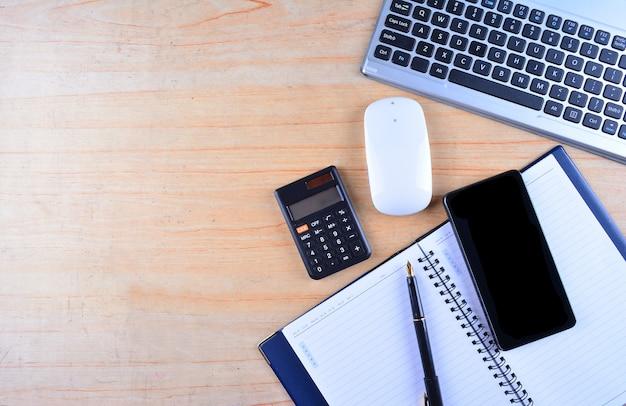 Teclado e mouse, caneta-tinteiro, caderno, calculadora e smartphone em uma mesa