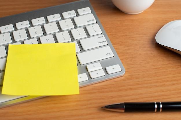 Teclado e mouse com blocos de notas e caneta amarelos