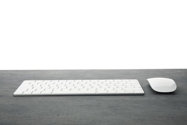 Teclado e mouse na mesa de madeira isolados no fundo branco