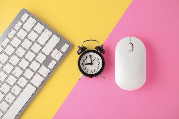 Teclado e mouse sem fio com relógio em fundo rosa amarelo
