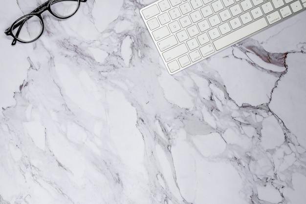Teclado e óculos em superfície de mármore