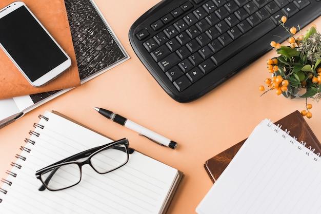 Teclado e smartphone perto de artigos de papelaria