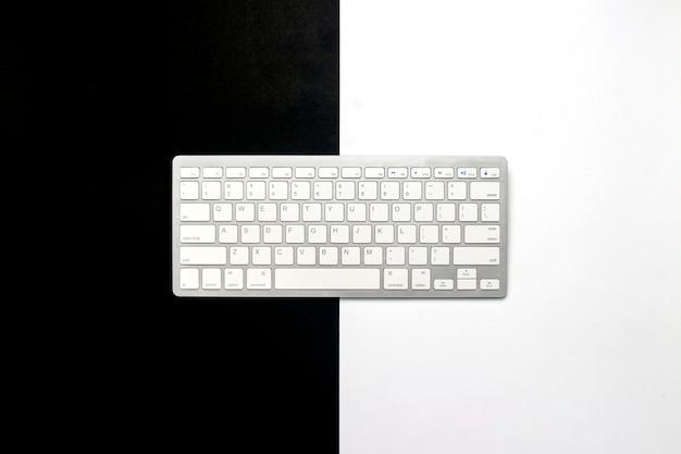 Teclado em um fundo preto e branco. o conceito de rede escura e a internet usual, a diferença, a compra. vista plana leiga, superior.