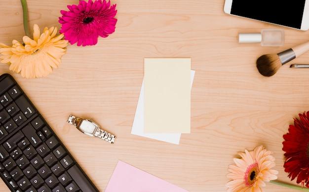 Teclado; flor gerbera; relógio de pulso; papel em branco; verniz para unhas; pincel de maquiagem e celular na mesa de madeira