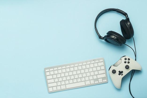 Teclado, fones de ouvido e gamepad sobre um fundo azul. . conceito de jogos de computador, entretenimento, jogos, lazer. vista plana, vista superior