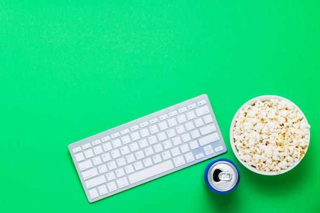 Teclado, lata com uma bebida e uma tigela de pipoca em um fundo verde. o conceito de assistir filmes, programas de tv, shows, esportes online. vista plana, vista superior