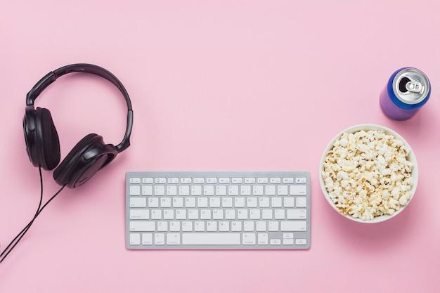Teclado, lata com uma bebida, fones de ouvido e uma tigela de pipoca em um fundo rosa. o conceito de assistir filmes, programas de tv e programas online, formato ppv. vista plana leiga, superior.
