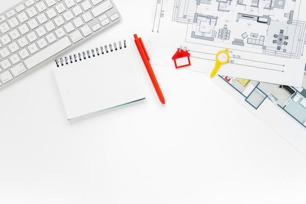 Teclado; leiteria espiral e blueprint sobre a mesa branca