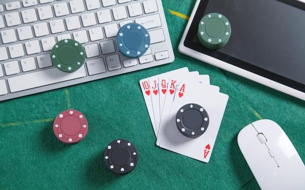 Teclado, mouse, cartas de jogar e chips de computador. casino online Foto Premium