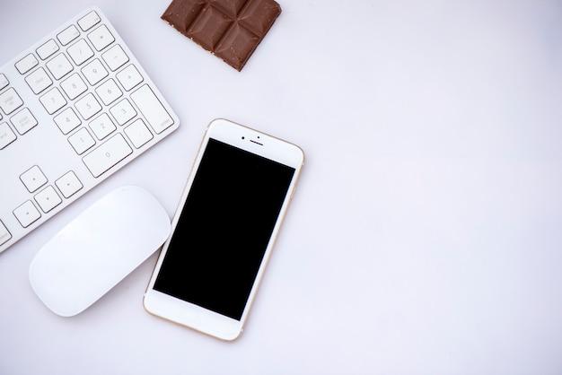 Teclado, mouse, chocolate e celular colocado em um fundo branco