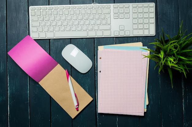 Teclado, mouse e notebook na mesa escura