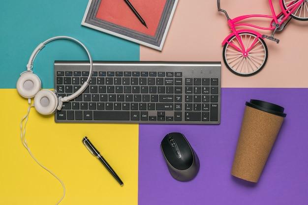 Teclado, mouse, fones de ouvido, um copo de café e uma pequena bicicleta em um fundo multicolorido. local de trabalho do designer.