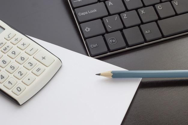 Teclado, notebook e calculadora em cima da mesa, vista superior