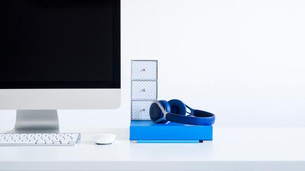 Teclado perto de monitor, mouse de computador e fones de ouvido na mesa
