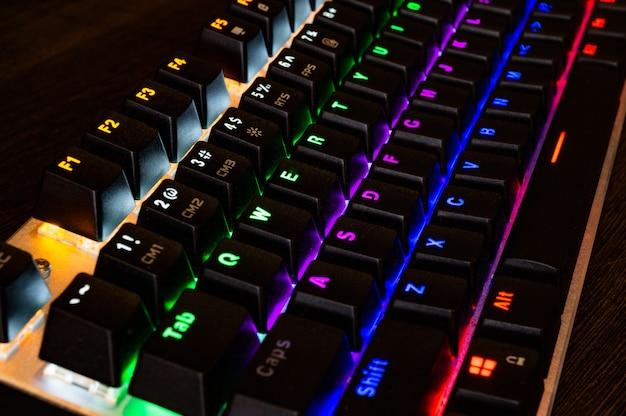 Teclado rgb mecânico de jogos profissionais multicoloridos em cima da mesa