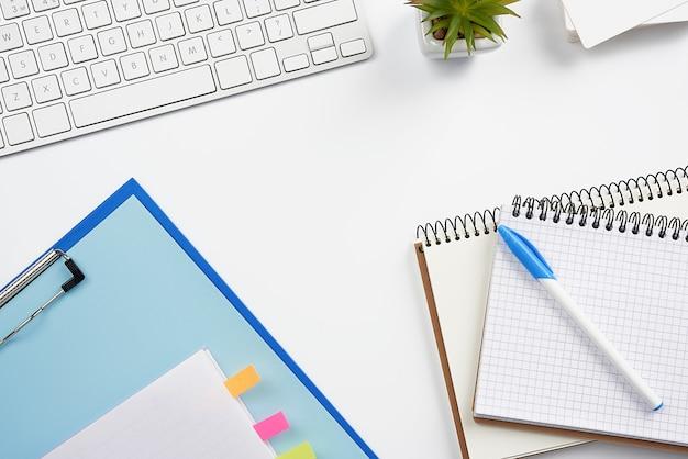 Teclado sem fio branco, uma pilha de cadernos, plantas verdes em vasos e um mouse, local de trabalho de um freelancer