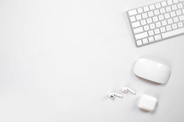 Teclado sem fio e mouse e fones de ouvido em cima da mesa