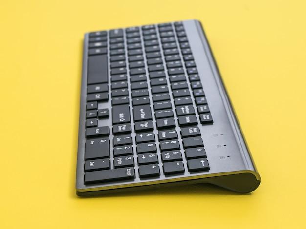 Teclado sem fio moderno em uma mesa amarela. dispositivos periféricos para o computador.