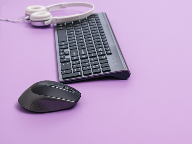 Teclado sem fio, mouse e fones de ouvido brancos sobre uma mesa de luz. dispositivos periféricos para o computador.