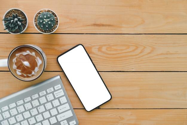 Teclado sem fio telefone celular cactus e cappuccino quente descansando em uma mesa de escritório de madeira marrom filmado de um ângulo alto, usado para anunciar produtos e mensagens