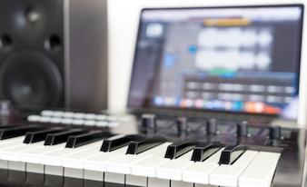 Teclado sintetizador deitado no desktop de trabalho de estúdio de música