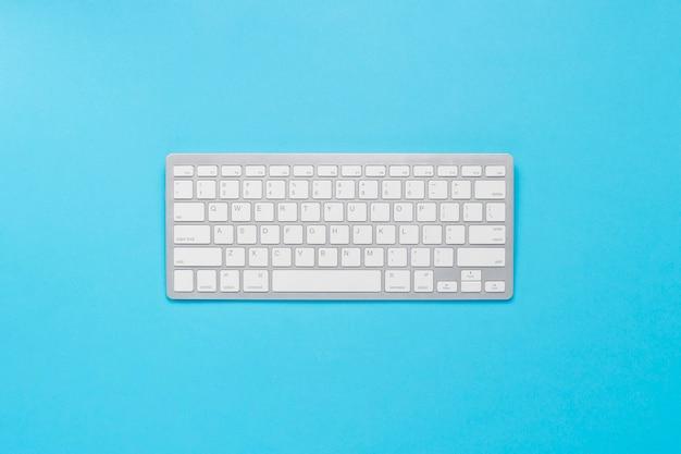 Teclado sobre um fundo azul. conceito de negócio, escritor, freelancer, jornalista. vista plana leiga, superior.