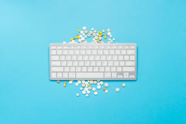 Teclado, vitaminas e comprimidos em um fundo azul. o conceito de compra de vitaminas, medicamentos, pílulas na internet, pedido via internet. vista plana leiga, superior.